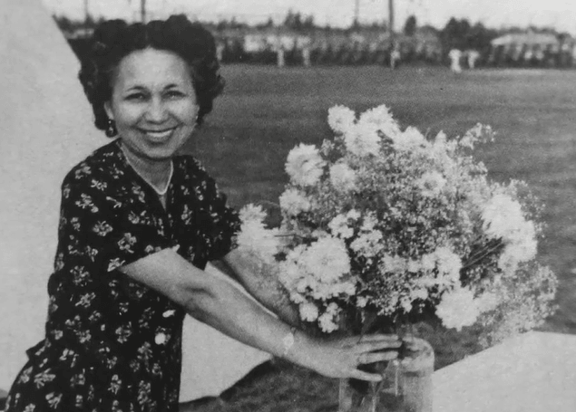 Black and white photograph of a woman in a dark floral dress placing a bouquet of flowers in a clear