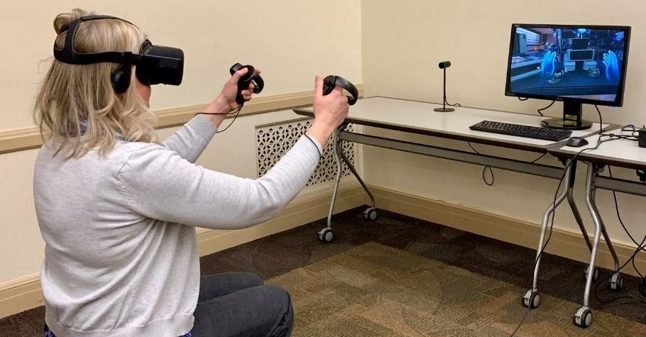a photo of a woman seated on a chair using the Oculus Rift headset and controllers