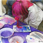 Person with pink hair creating art with bubbles.