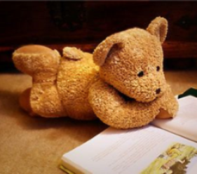 Teddy bear posed reading a book.