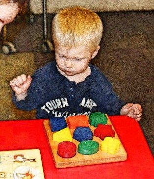 Child studying a colorful block puzzle.