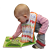 Photograph of a waddler examining a board book.