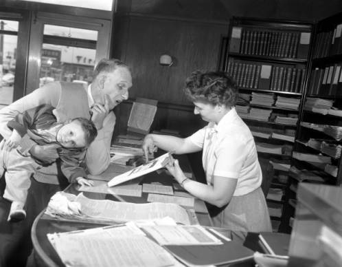 Historic photo of librarian and customers at Everett Public Library