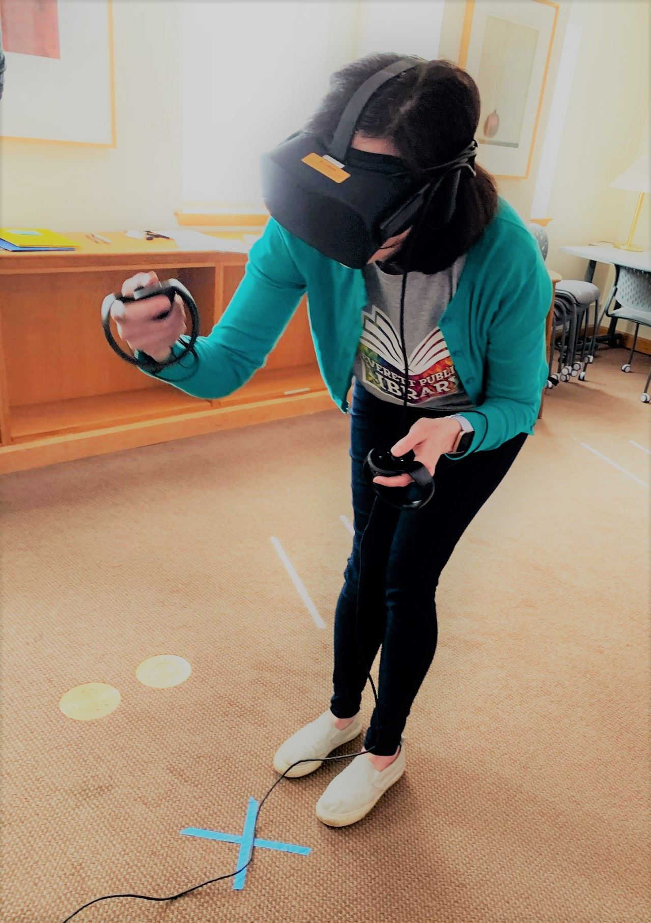 Photo of woman trying out a virtual reality headset at the library.
